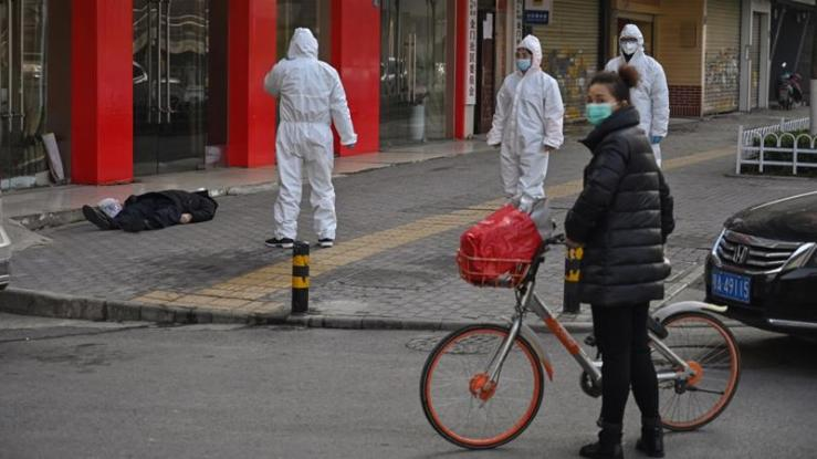 Officials in protective suits check on an elderly man wearing a facemask who collapsed and died on a street near a hospital in Wuhan on Thursday [Hector Retamal/AFP]